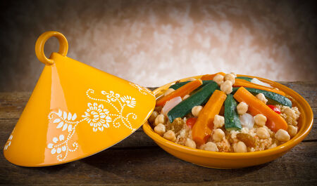 dialect: Vegetable Tajine with cous cous on wooden table. Stock Photo