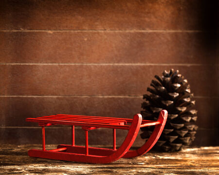 Wooden red sled with brown pine cone on wood background photo