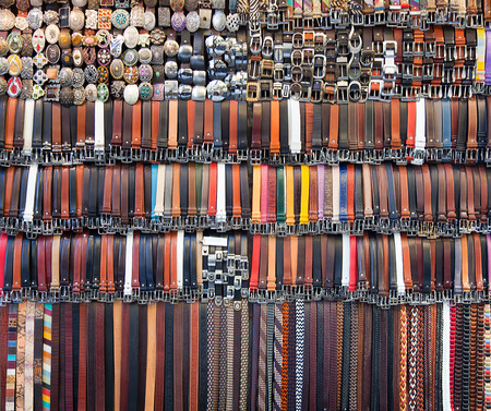 suede belt: Many colored leather belts on a market. Stock Photo