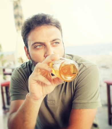 near beer: Young man drinking beer sitting at the restaurant near the sea. Stock Photo