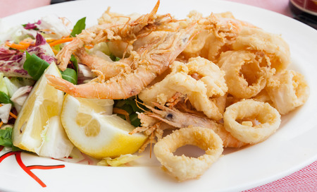 Fried shrimp and squid with lemon, italian food. Foto de archivo