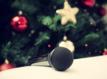 Black microphone on white leather sofa near the Christmas tree. Concept of Christmas sung music. photo