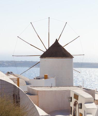 Windmill in Oia, Santorini. Oia is a village in the north west edge of the Santorini island with white houses. photo