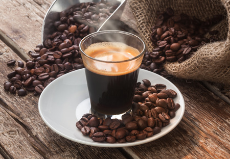 neapolitan: Espresso coffee in glass cup with coffee beans on wooden table.