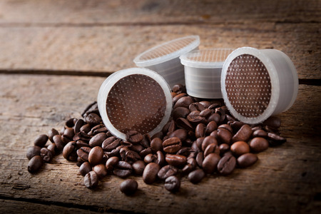 Coffee beans with pods on wooden table. Editorial