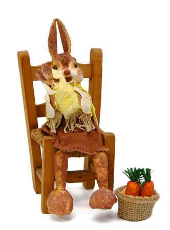 Rabbits papier sitting on chair straw on white background. photo