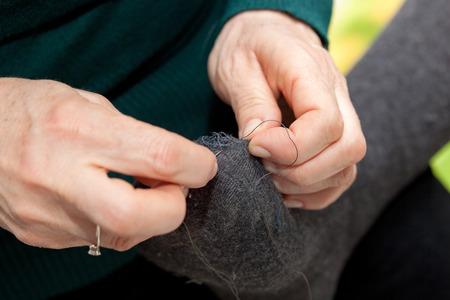 darn: Moglie darning sock with hole to her husband Stock Photo