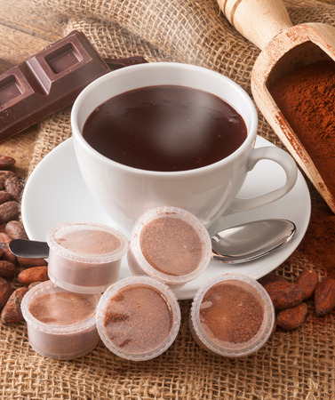 Cup of hot chocolate with pods, cocoa powder, cocoa beans and pieces of chocolate. photo