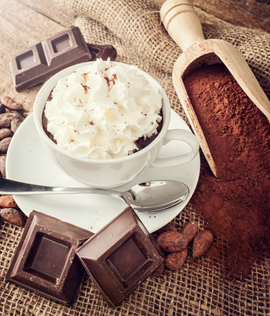 Cup of hot chocolate with whipped cream, cocoa powder, cocoa beans and pieces of chocolate. photo