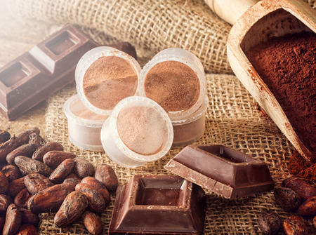 cocoa beans: Capsules of chocolate with cocoa powder, cocoa beans and pieces of chocolate. Stock Photo