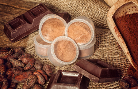 Capsules of chocolate with cocoa powder, cocoa beans and pieces of chocolate. photo