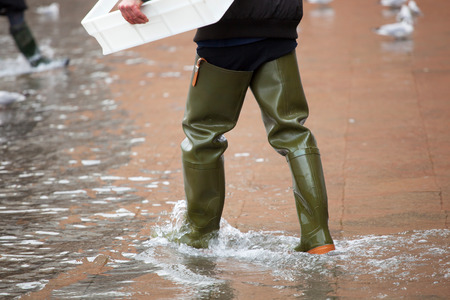 happens: Close Up of legs with boots due to the high water. This flood happens when there is high tide in Venice, Italy. Stock Photo