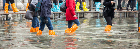 the flood tide: Close Up of legs with boots due to the high water. This flood happens when there is high tide in Venice, Italy. Editorial