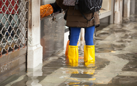 the flood tide: Close Up of legs with boots due to the high water. This flood happens when there is high tide in Venice, Italy. Stock Photo