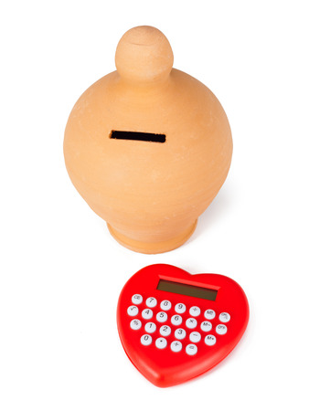 money box: Calculator heart shaped and money box. Concept of calculation and savings. Stock Photo