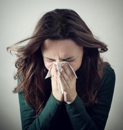 persona enferma: Mujer joven que sopla su nariz con un pa�uelo de papel sobre fondo gris. Foto de archivo