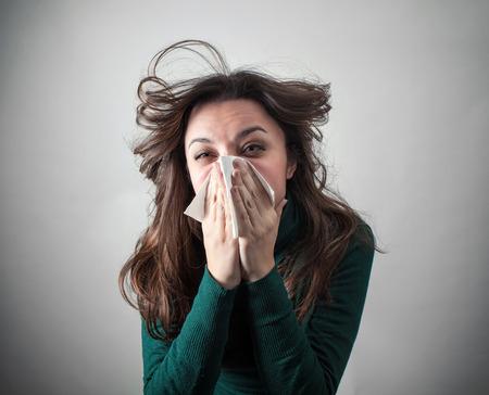 nariz: Mujer joven que sopla su nariz con un pa�uelo de papel sobre fondo gris. Foto de archivo