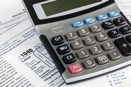 contributions: US Individual Tax Return Form 1040 close up with calculator.
