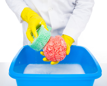 Metaphor of brainwashing, doctor washes the brain with the sponge.