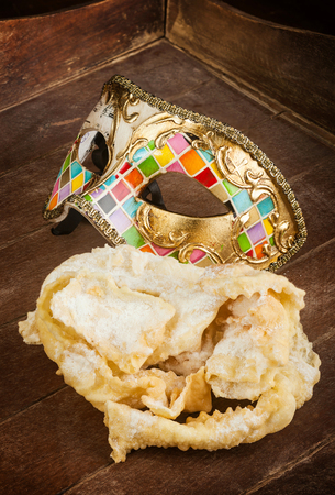 sugar veil: Typical fried pastry of italian carnival with venetian mask. These sweet are called in different ways, chiacchiere, Galani, cenci or frappe.