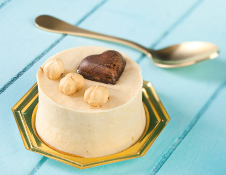 small cake: Small cake with hazelnuts and dark chocolate heart on blue wooden table. Stock Photo