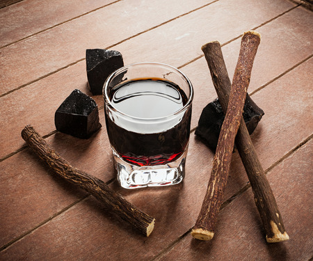 alcohol drinks: Licorice liqueur with pure blocks and roots on wooden table.