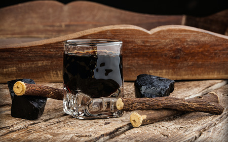 licorice: Licorice liqueur with pure blocks and roots on wooden table.