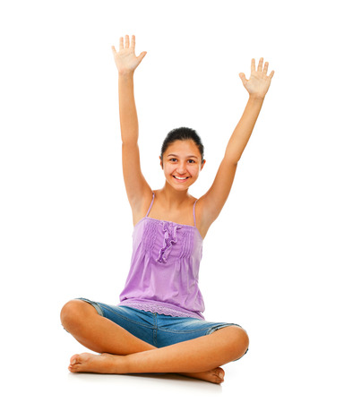 exultation: Sitting teenage girl while rejoices with arms up on white background Stock Photo