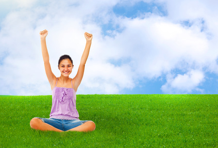 rejoices: Sitting teenage girl while rejoices with arms up in green grass with blue sky.