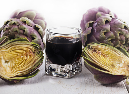 extract: Alcoholic drink with artichoke extract on wooden table. Stock Photo
