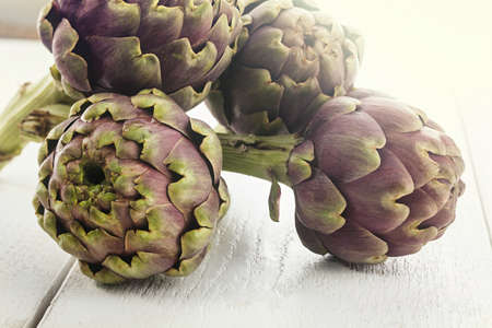 biological: Four biological raw artichokes on white wooden table.