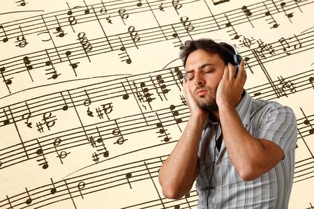 pentagramma musicale: Giovane uomo ascolta musica con le cuffie su sfondo di una partitura musicale.