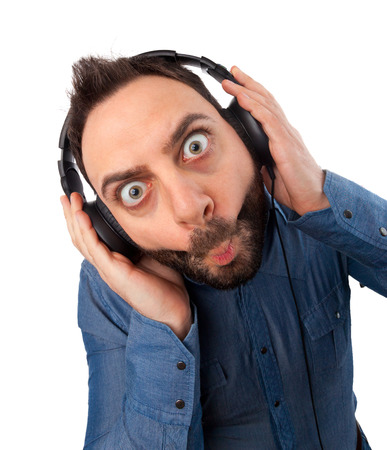 Young surprised man with headphones on white background. photo