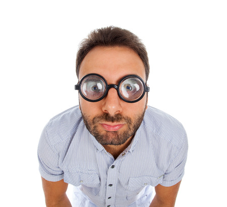 Young man with a surprised expression and thick glasses on white background. Stock Photo