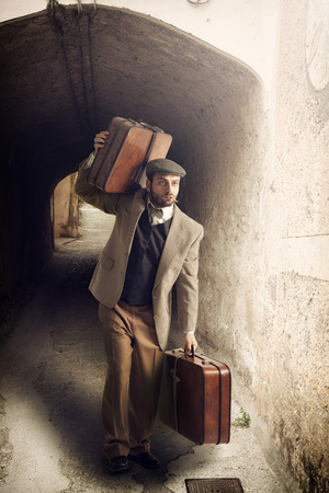 emigrant: Emigrant man with the suitcases in a small town.