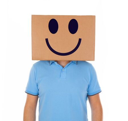 masquerader: Young man standing with a cardboard box on his head with smiley face on white background. Stock Photo