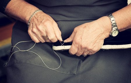 woman handle success: Female shoemaker sews shoes on his knees.