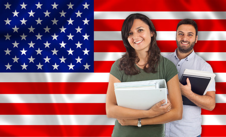 internships: Couple of young students with books over United States flag