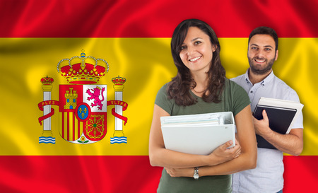 spanish language: Couple of young students with books over spanish flag Stock Photo