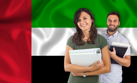 parlance: Couple of young students with books over United Arab Emirates flag Stock Photo