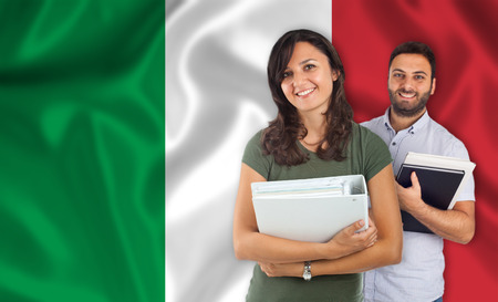 parlance: Couple of young students with books over italian flag