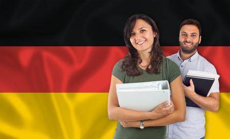 Paar van jonge studenten met boeken over Duitse vlag