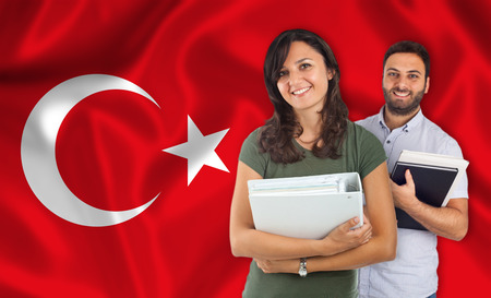 internships: Couple of young students with books over turkish flag