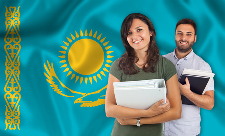 parlance: Couple of young students with books over Kazakh flag