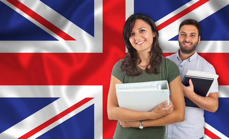 idiomas: Pareja de jóvenes estudiantes con los libros sobre la bandera de Inglés