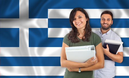 parlance: Couple of young students with books over Greek flag Stock Photo