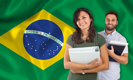 parlance: Couple of young students with books over brazilian flag