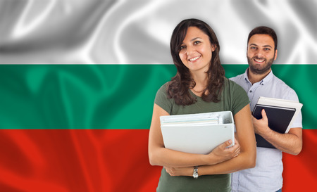 internships: Couple of young students with books over Bulgarian flag