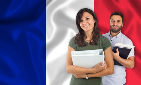 parlance: Couple of young students with books over french flag
