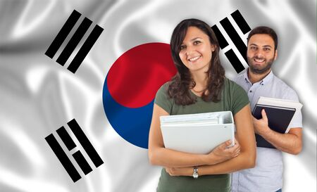 internships: Couple of young students with books over south Korean flag